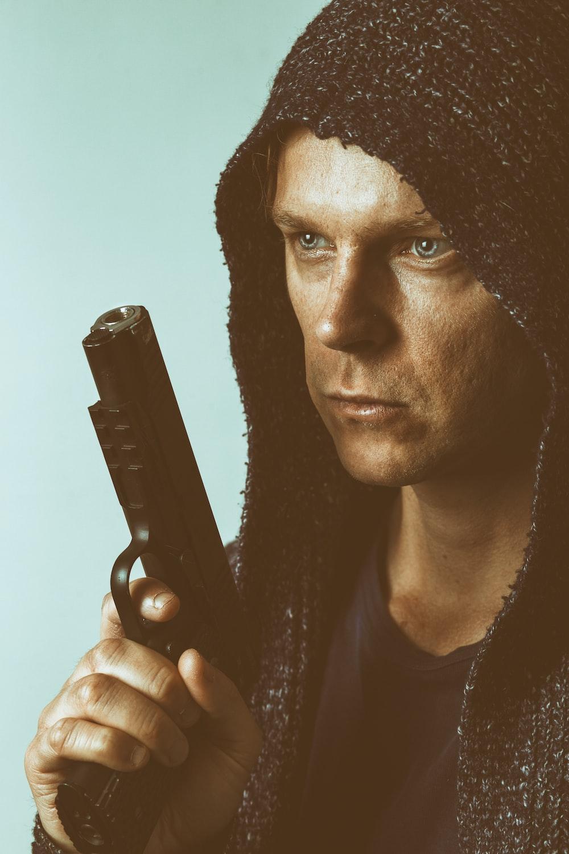 man holding black semi automatic pistol
