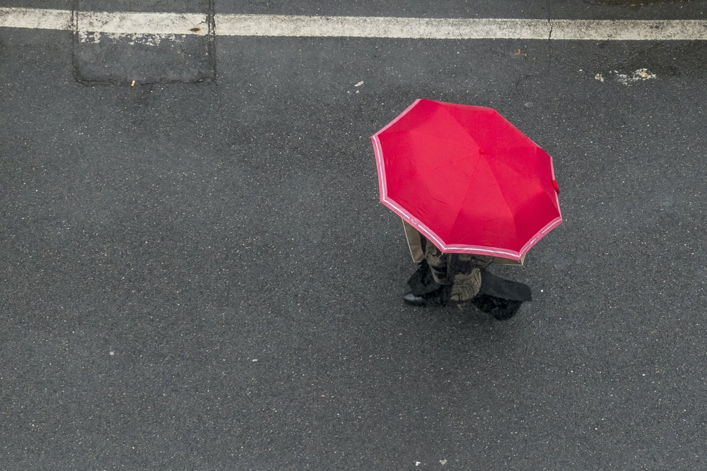 person in red umbrella walking on gray asphalt road during daytime
