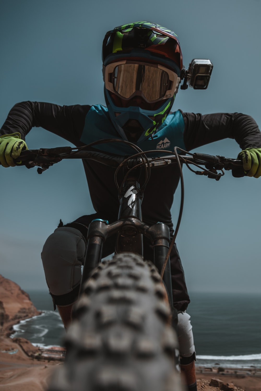 person in black jacket riding black mountain bike during daytime