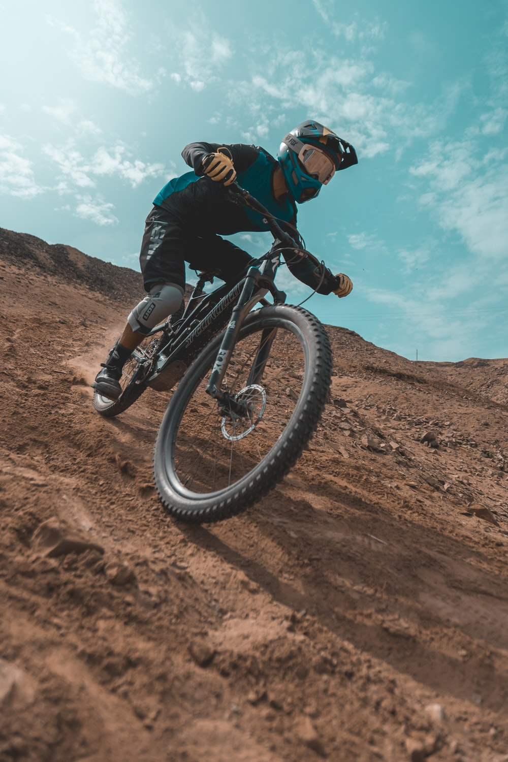 man rides with mountain bike on a steep downhill track and is wearing flat pedal MTB shoes