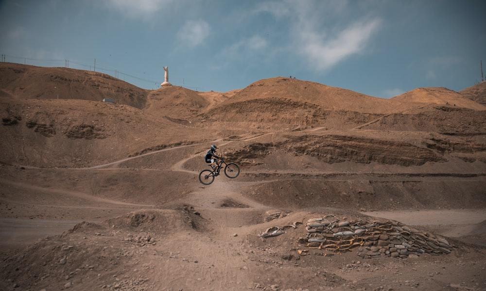man in black jacket riding bicycle on brown sand during daytime