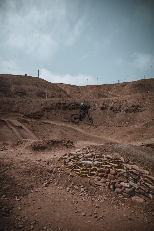 man riding on black motorcycle on brown rocky mountain during daytime