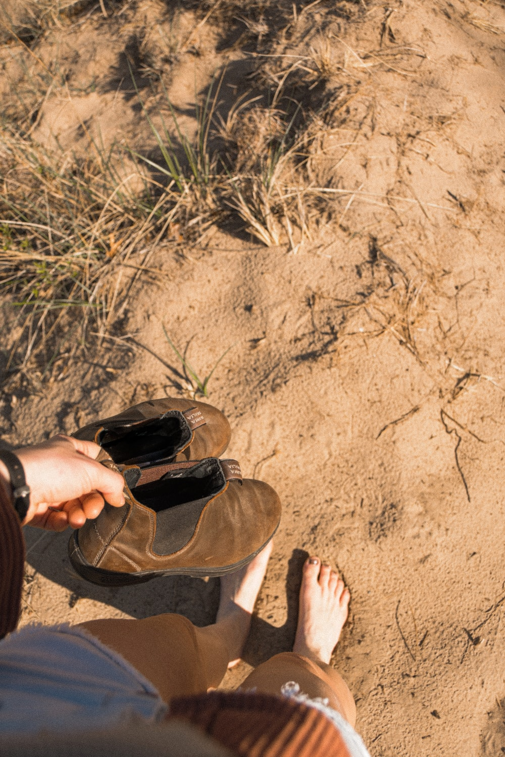 person in brown pants sitting on brown sand during daytime