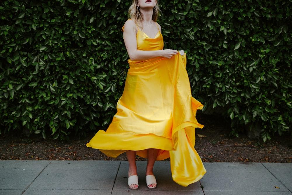 woman in yellow sleeveless dress standing on gray concrete floor
