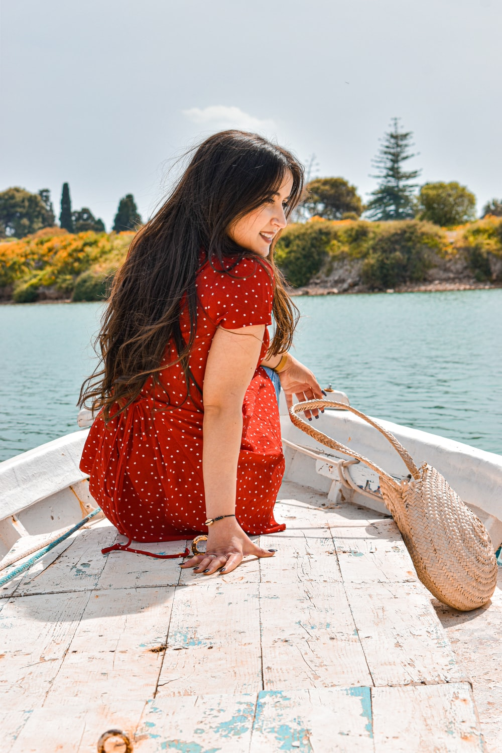 girl in red dress standing on dock during daytime