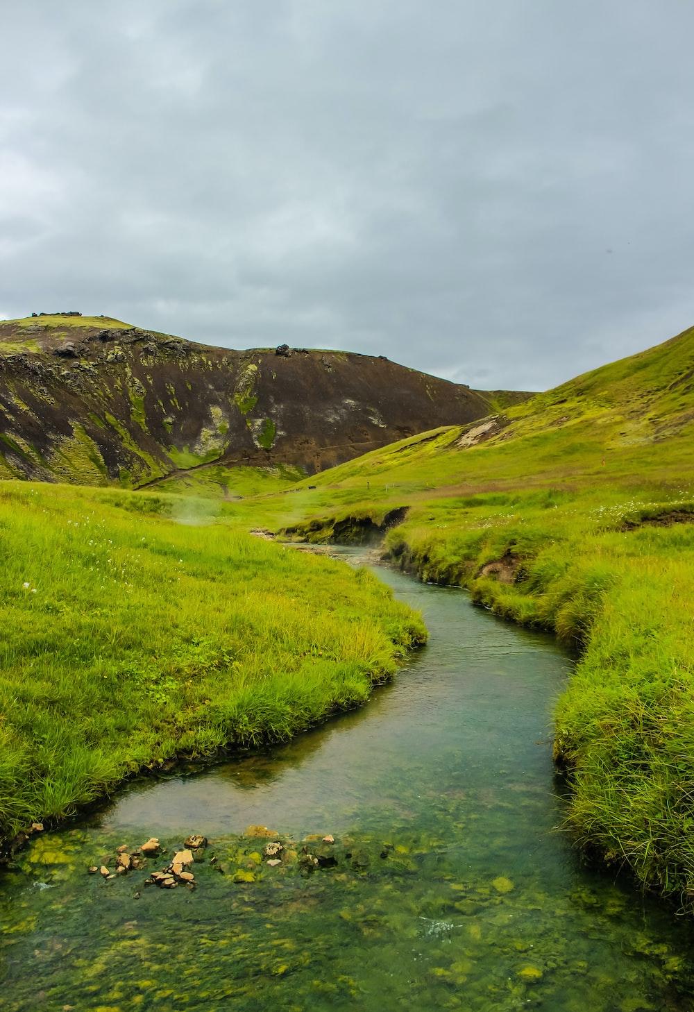green grass field near river under cloudy sky during daytime