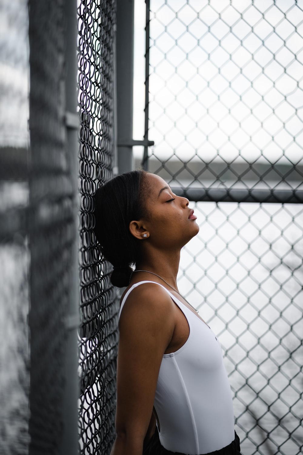 woman in white tank top leaning on chain link fence