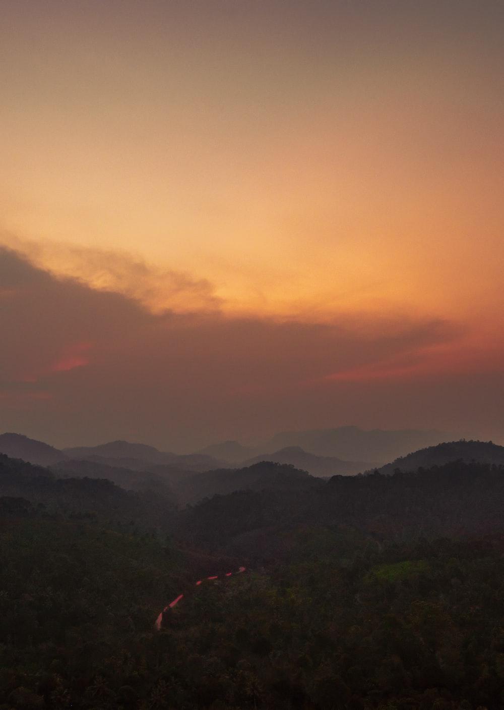 green mountains under orange sky