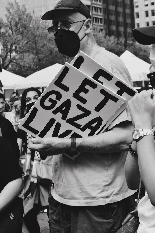 man holding white and black love print signage