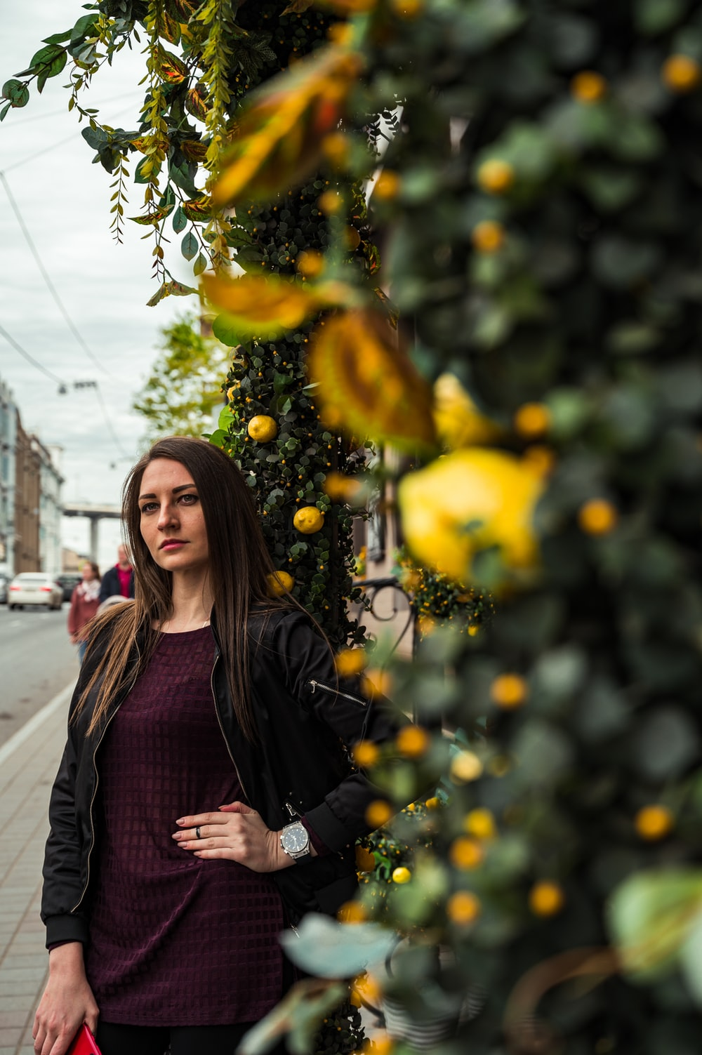 woman in black leather jacket standing beside yellow leaves during daytime