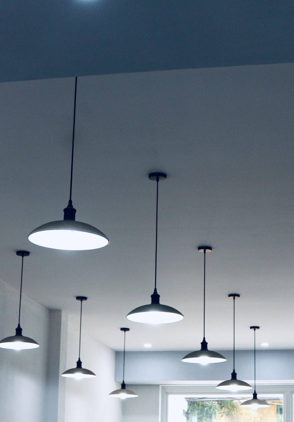 black pendant lamps turned on during daytime