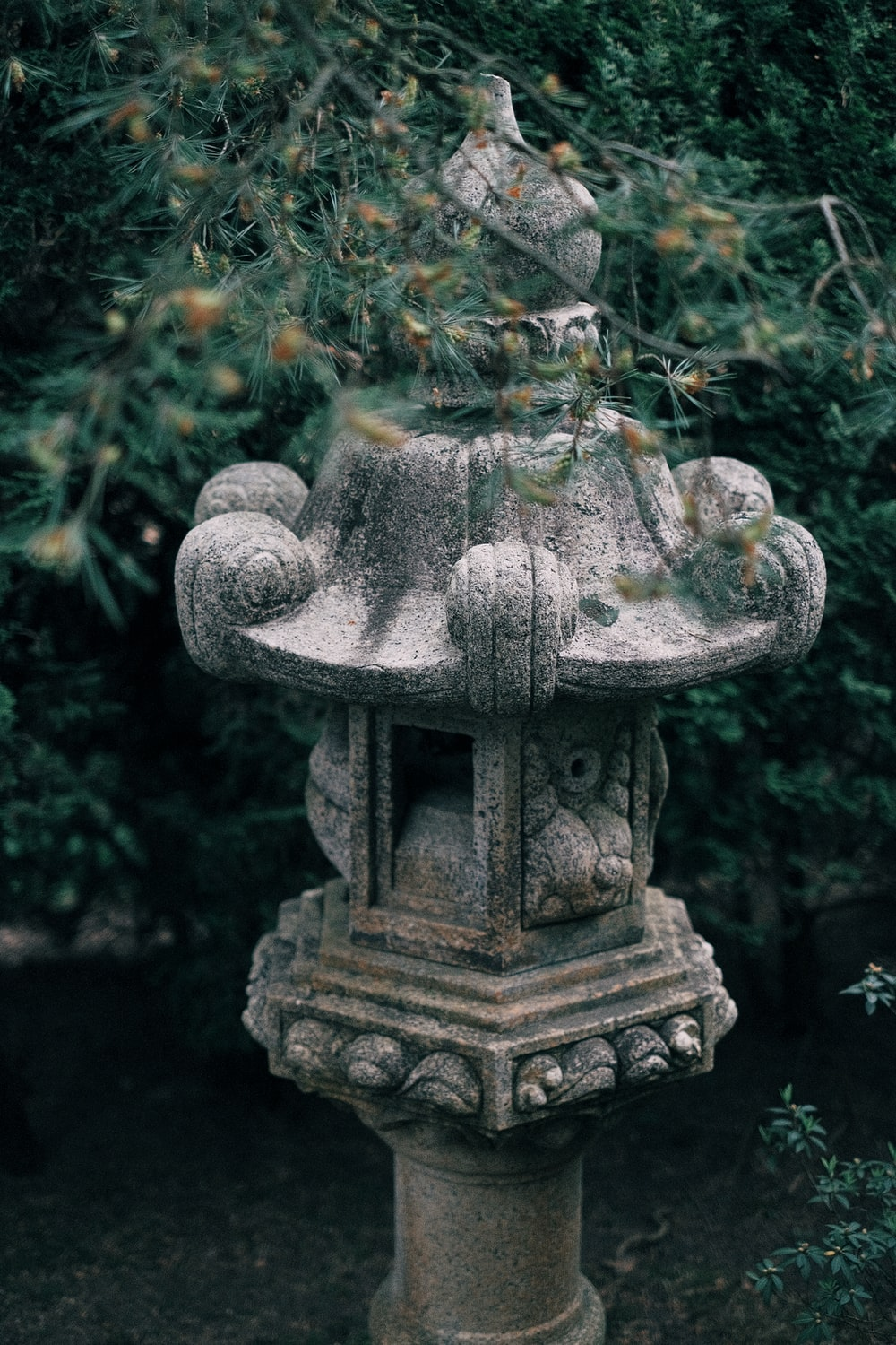 gray concrete statue surrounded by green leaves