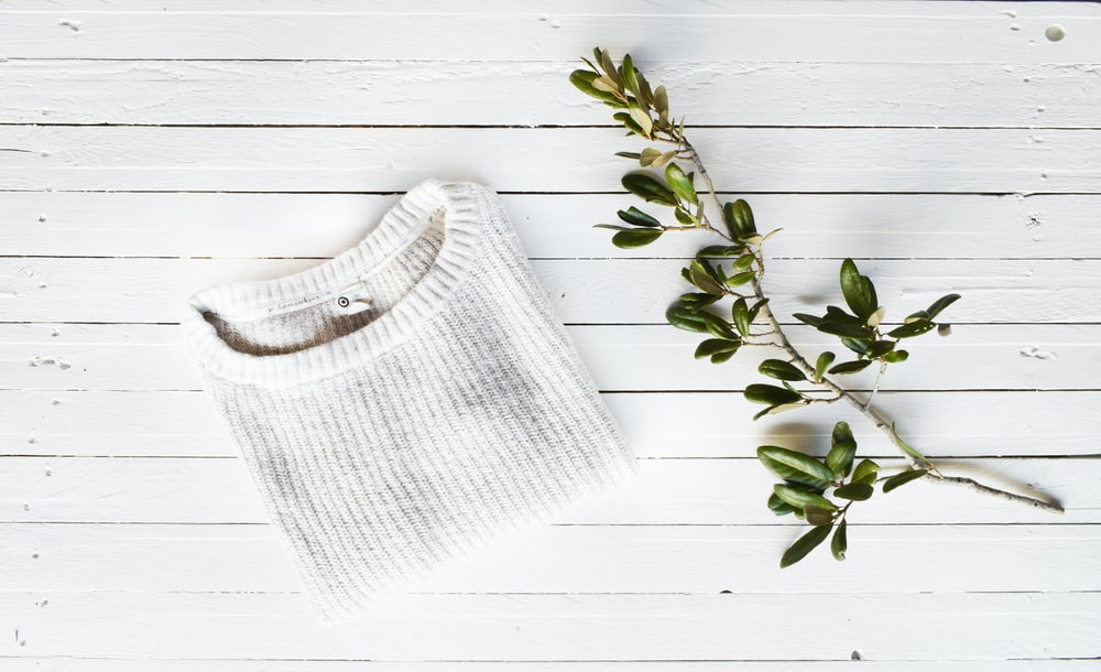 white knit sweater on white wooden surface