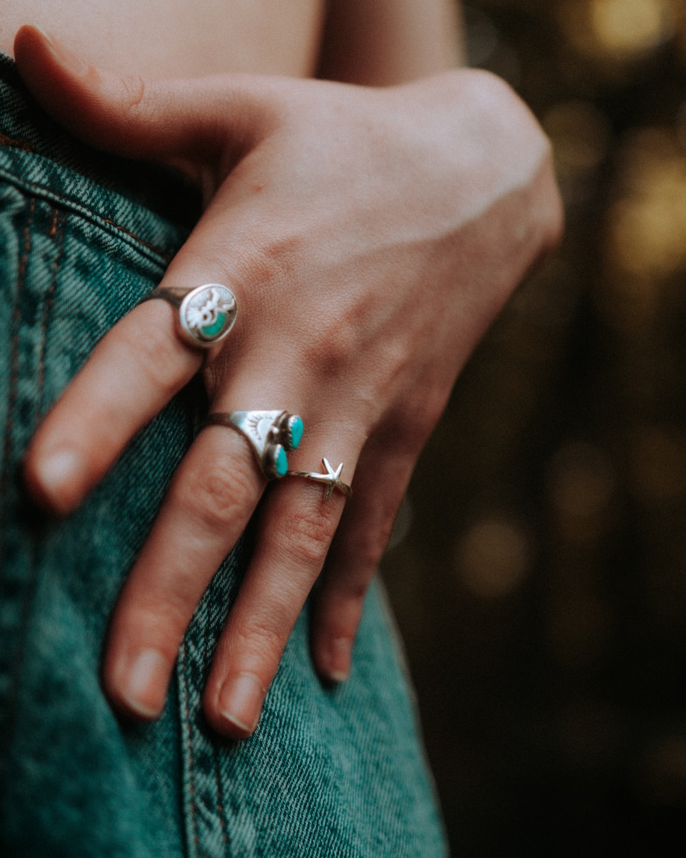person wearing silver and blue gemstone ring
