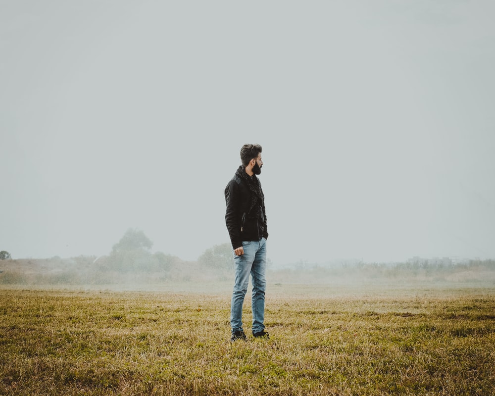 man in black jacket and blue denim jeans standing on green grass field during daytime