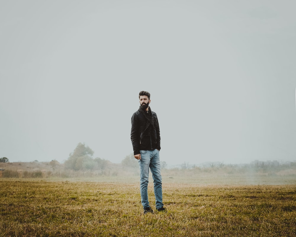 man in black jacket standing on green grass field during daytime