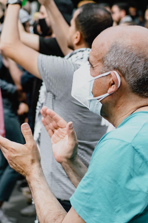 man in blue scrub shirt wearing white face mask