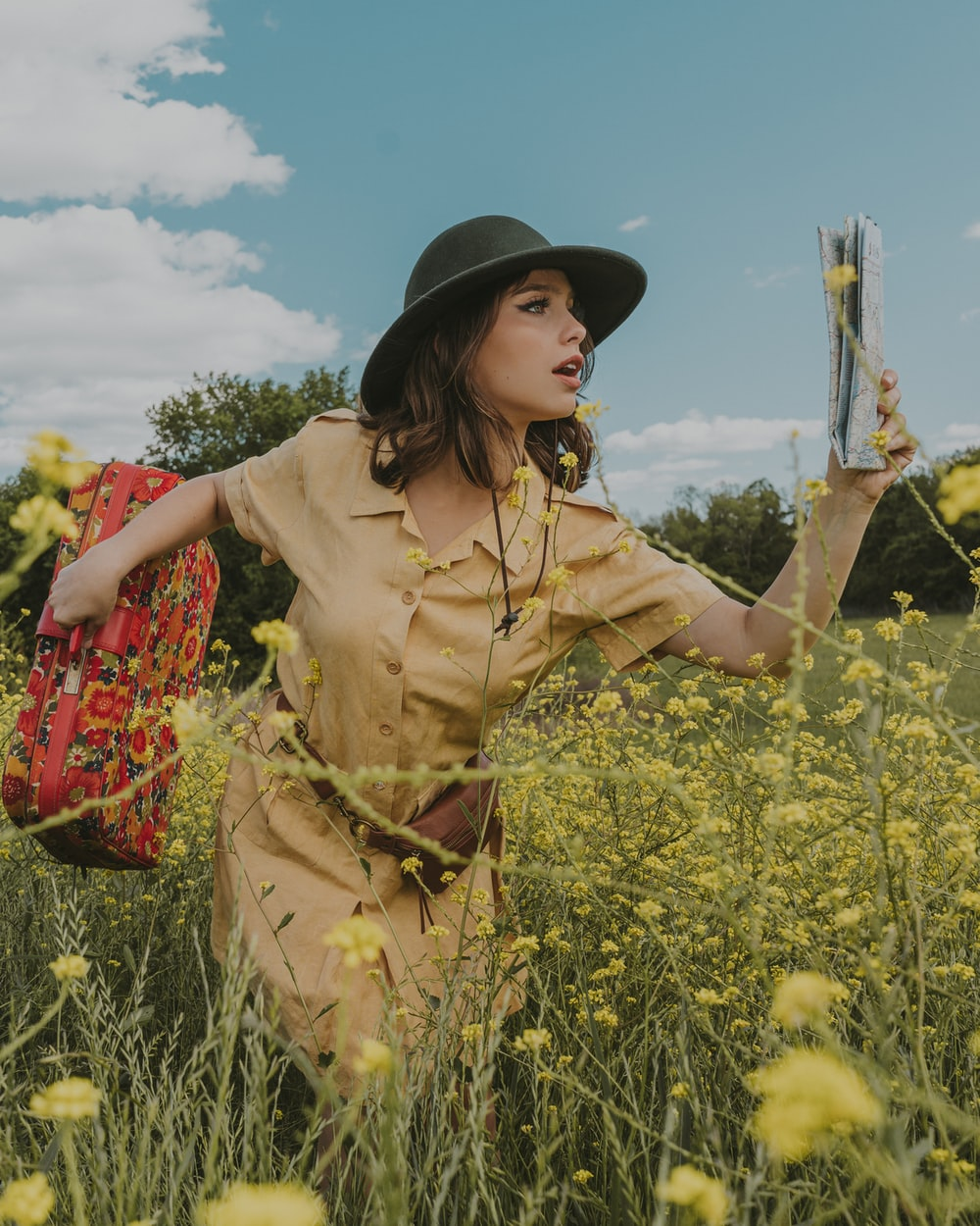 woman in brown dress and black hat standing on yellow flower field during daytime