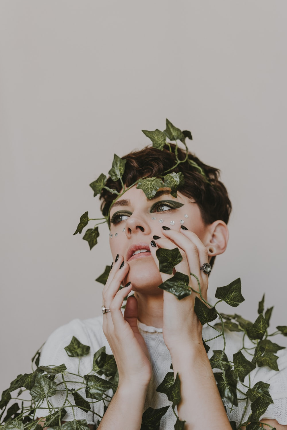 woman in white shirt holding green leaves