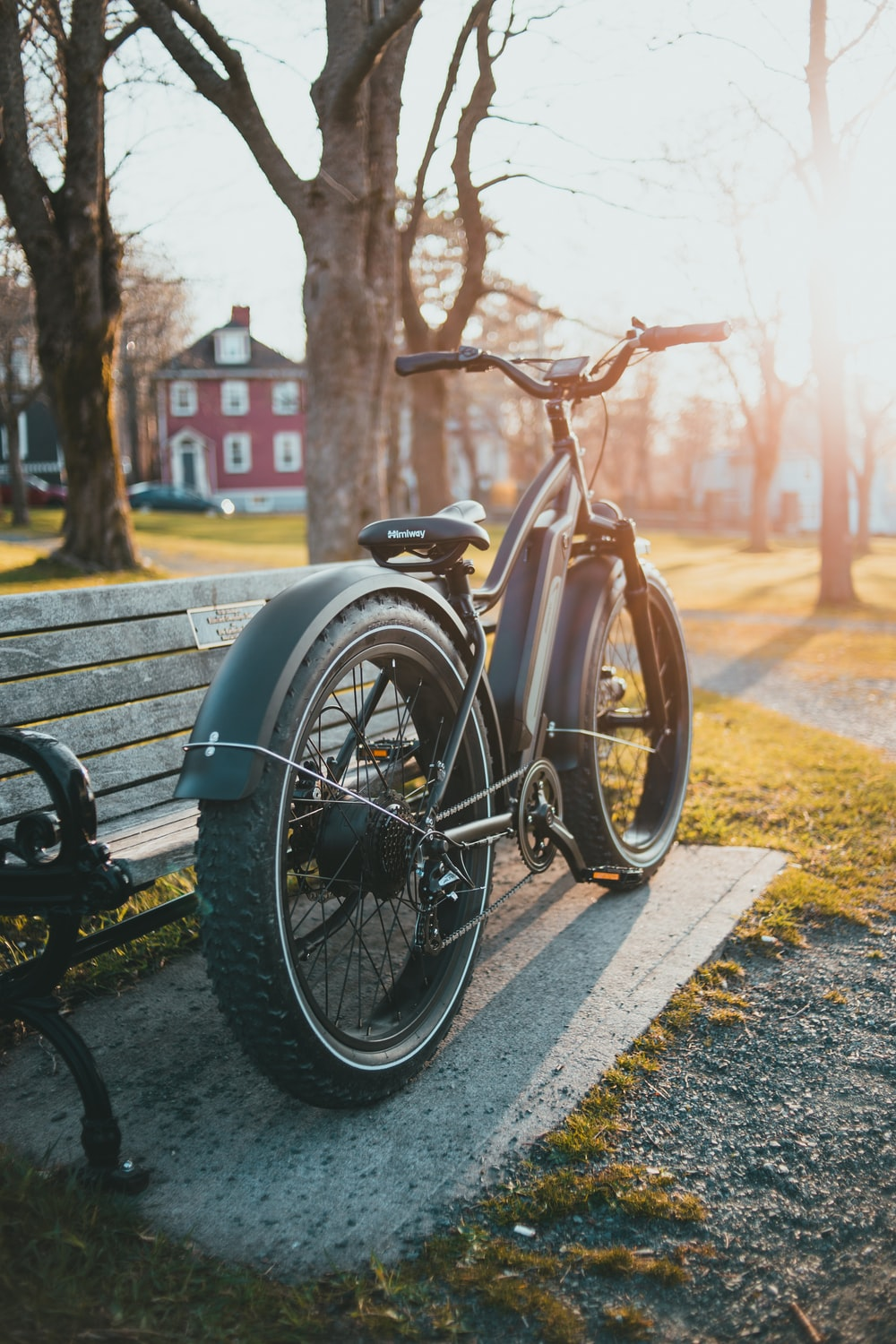 black bicycle parked beside brown wooden bench during daytime