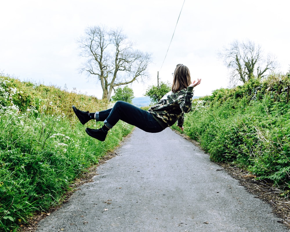 girl in hoodie and blue denim jeans levitating on gray concrete lane during daytime