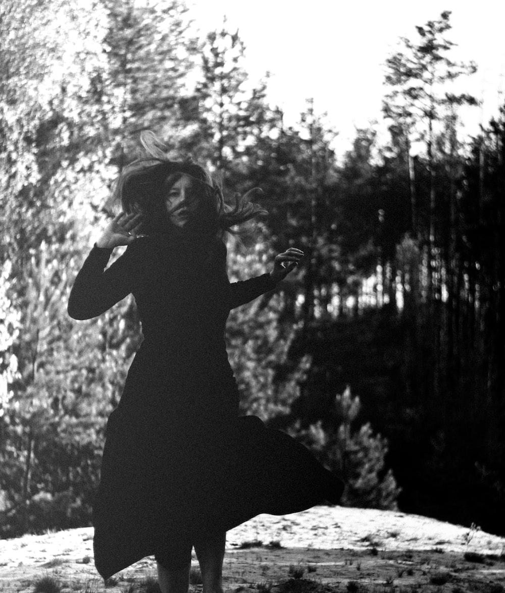 woman in black dress sitting on rock