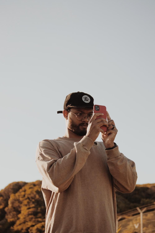 man in brown coat wearing black cap holding black smartphone