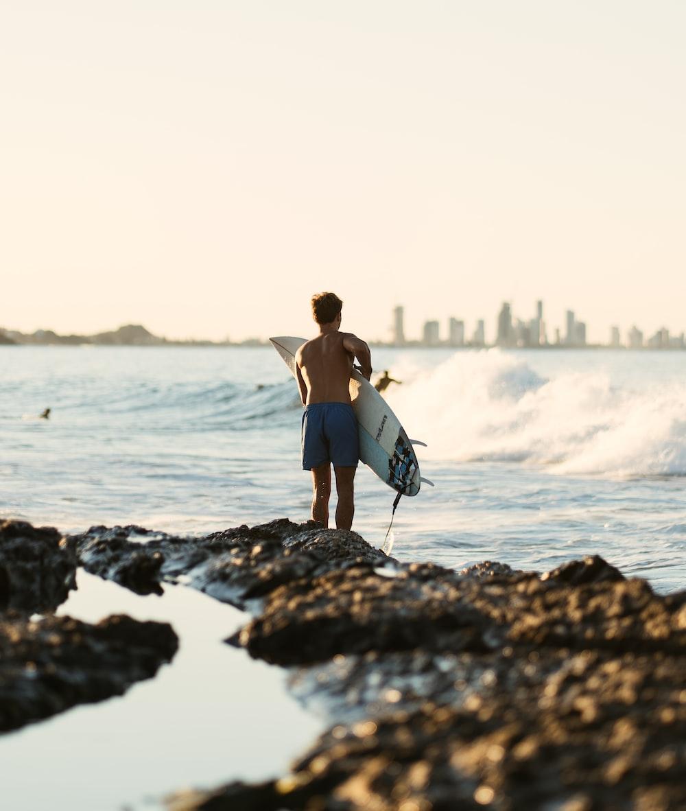 woman in blue bikini holding white surfboard standing on rock near sea during daytime