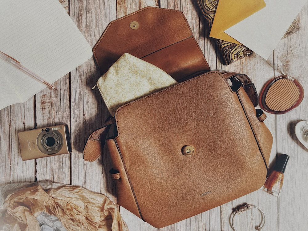brown leather sling bag beside silver and gold camera