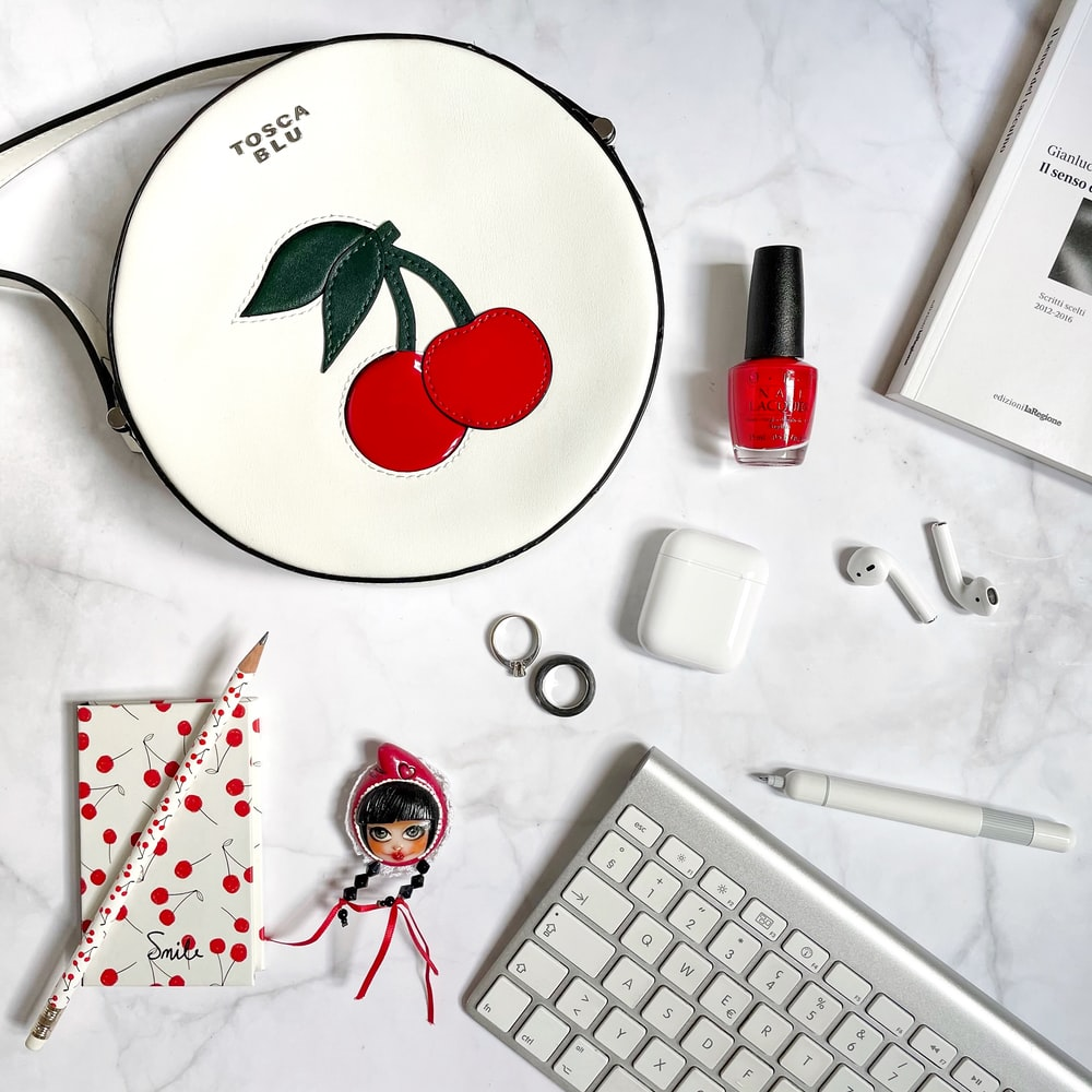 white and red floral round plate beside white computer keyboard and red and white click pen