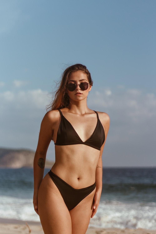 woman in black bikini wearing sunglasses standing on beach during daytime