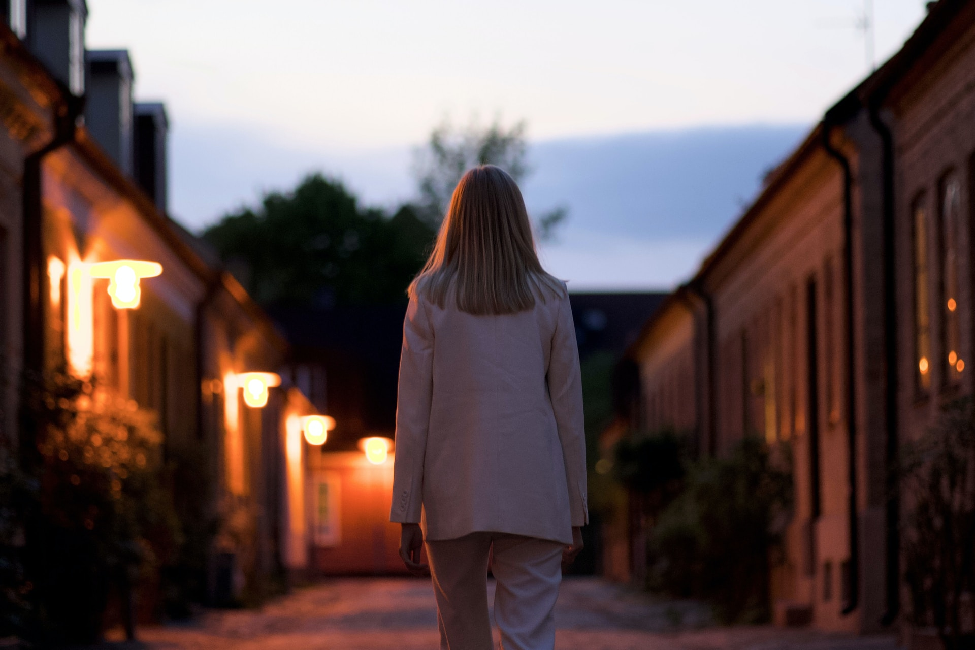 woman in white long sleeve shirt and gray pants standing on brown brick pathway during sunset
