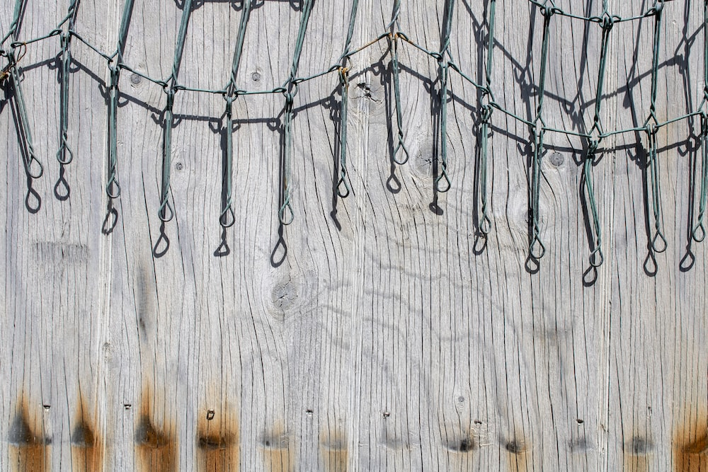 silver wire on wooden wall