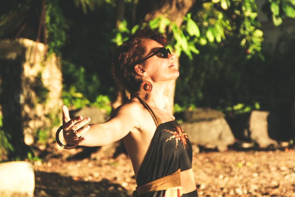 woman in black spaghetti strap top wearing black sunglasses