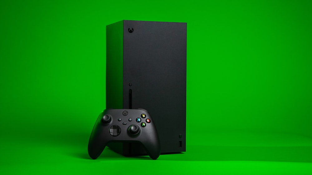 black xbox one console with controller