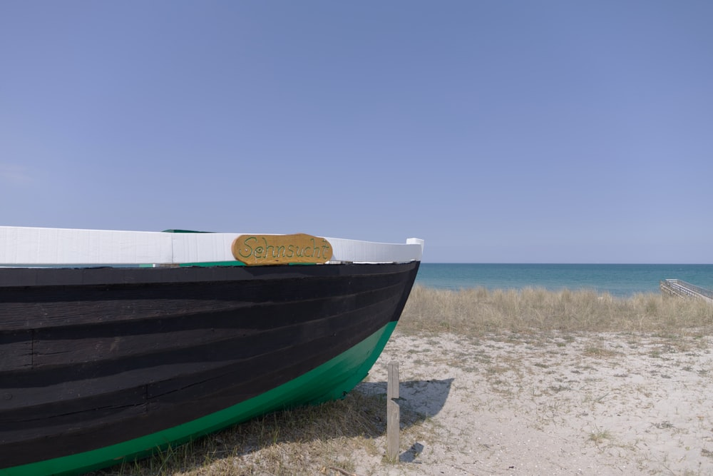 blue and white boat on beach shore during daytime