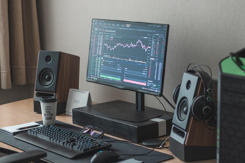 black flat screen computer monitor turned on beside black computer keyboard