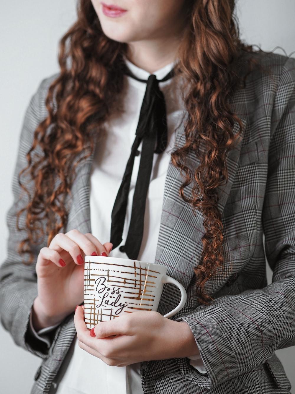 woman in gray blazer holding white and black ceramic mug