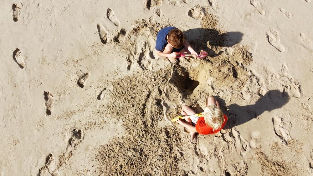2 boys lying on sand during daytime