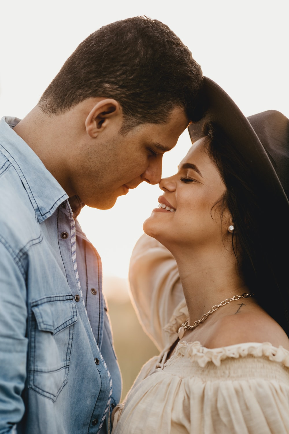 man in blue denim button up shirt kissing woman in white floral dress