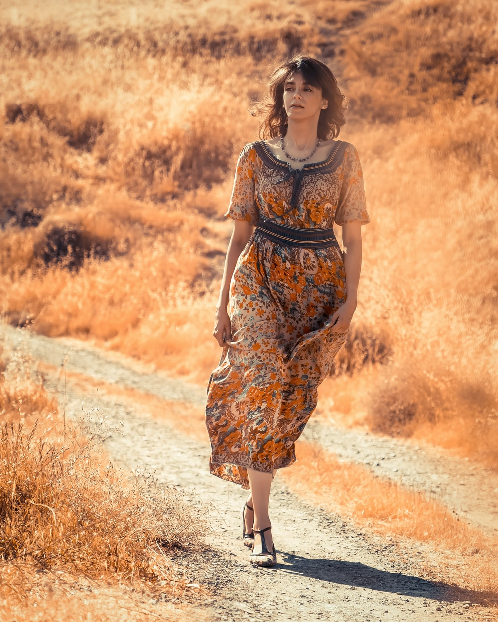 woman in brown and black floral dress standing on dirt road during daytime