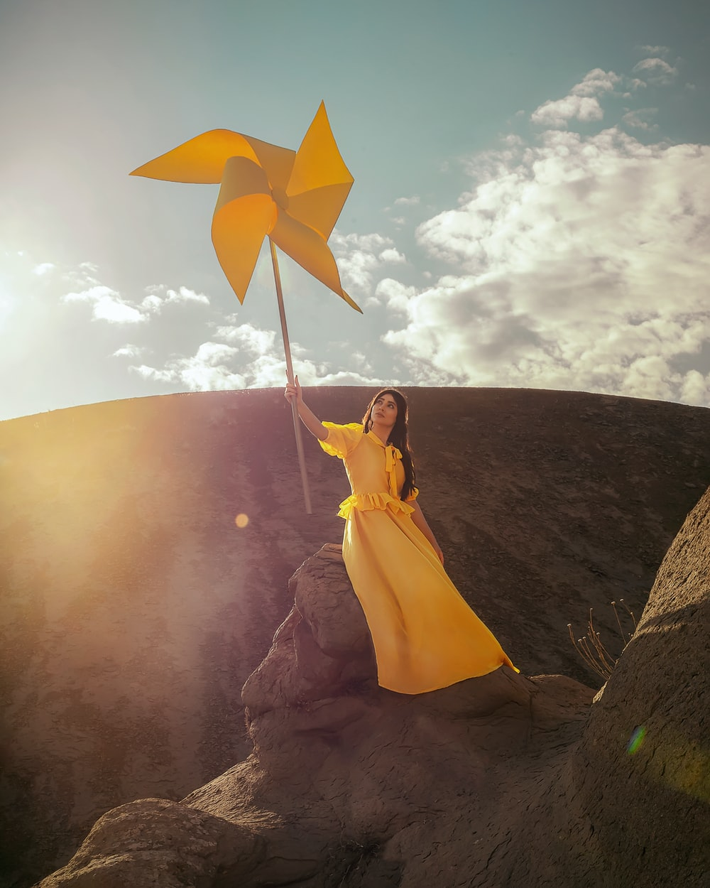 woman in yellow dress holding yellow umbrella
