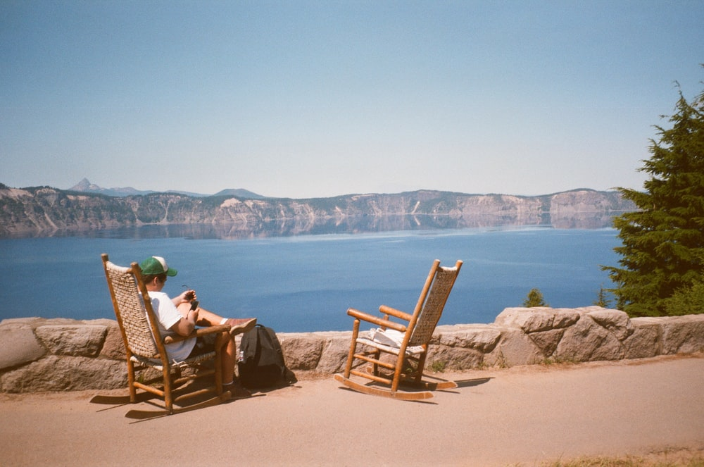 2 person sitting on brown wooden rocking chairs on brown sand near body of water during