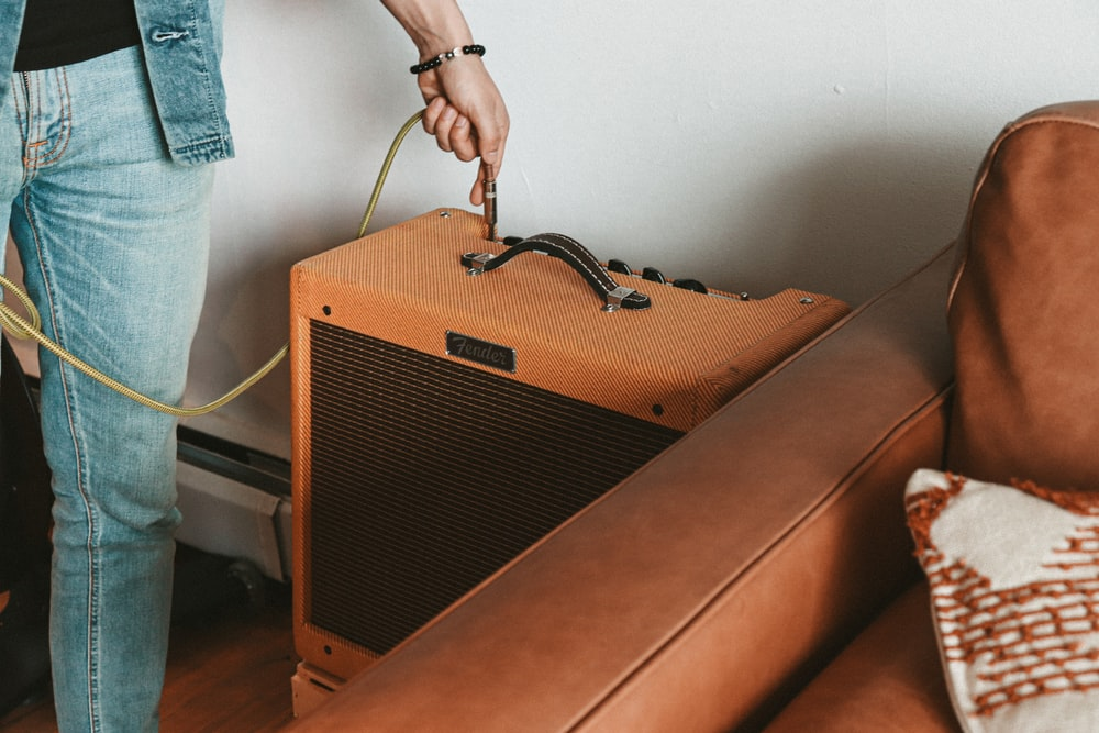 person holding brown guitar amplifier