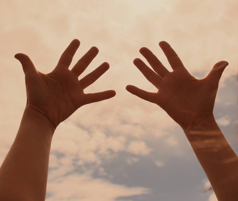 persons left hand under blue sky during daytime