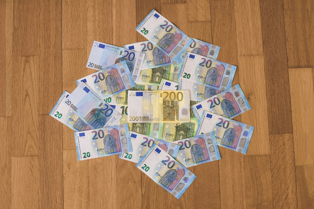 10 and 10 banknotes on brown wooden table