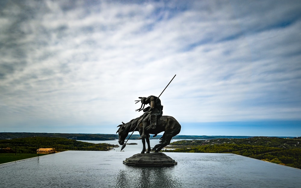 man riding horse statue under white clouds during daytime