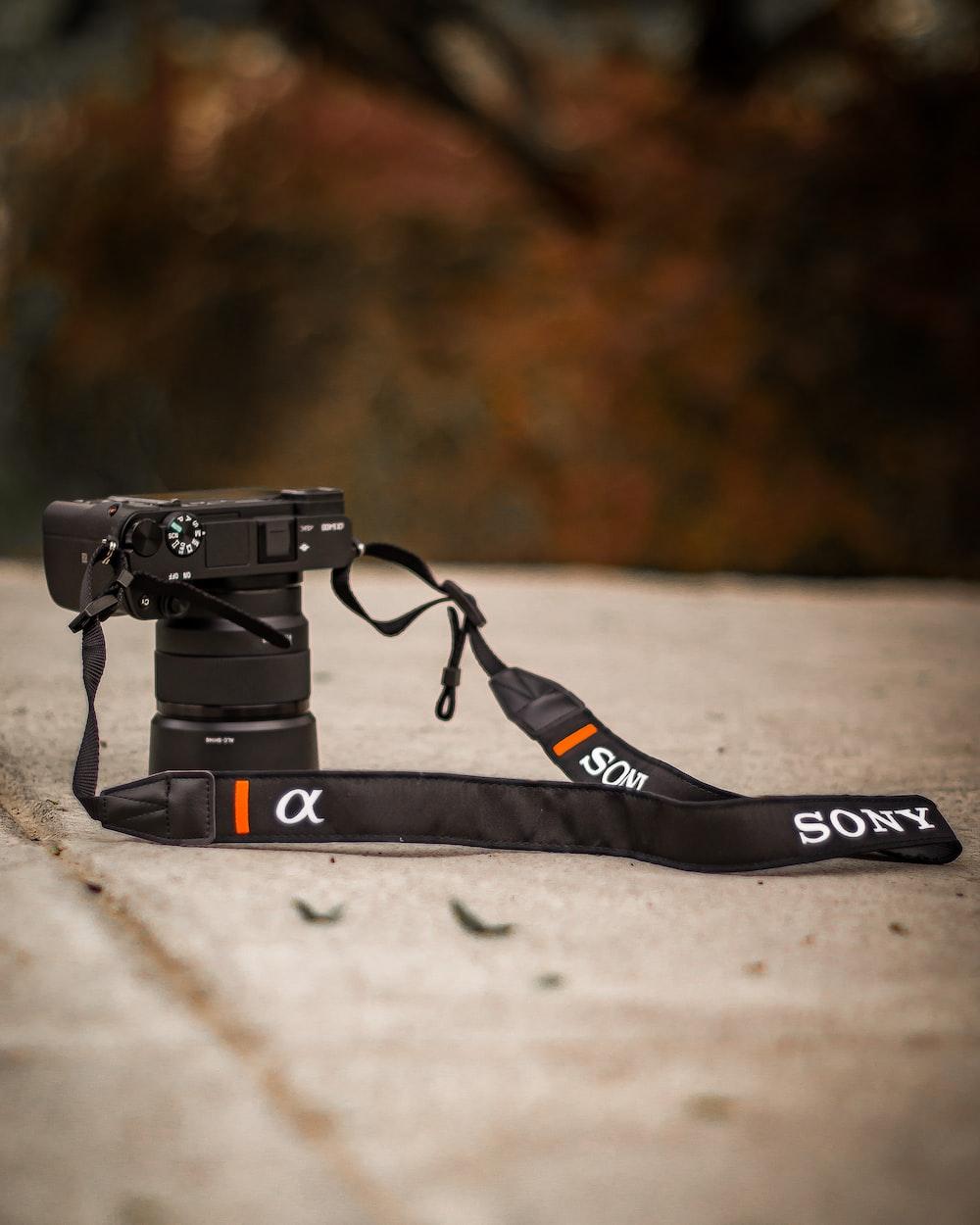 black nikon dslr camera on gray concrete floor