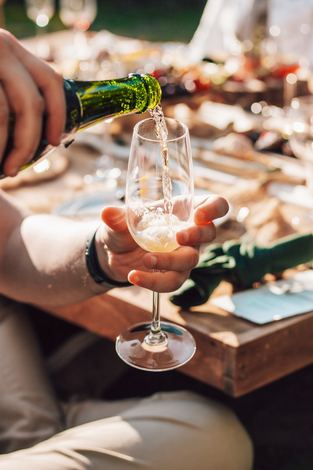 person holding green glass bottle pouring on clear wine glass