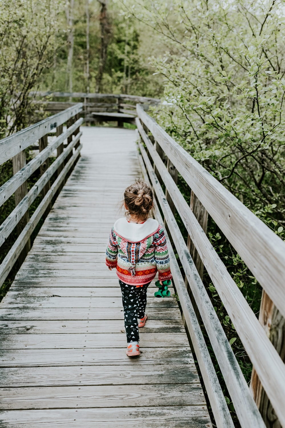 girl in white and red long sleeve shirt standing on wooden bridge